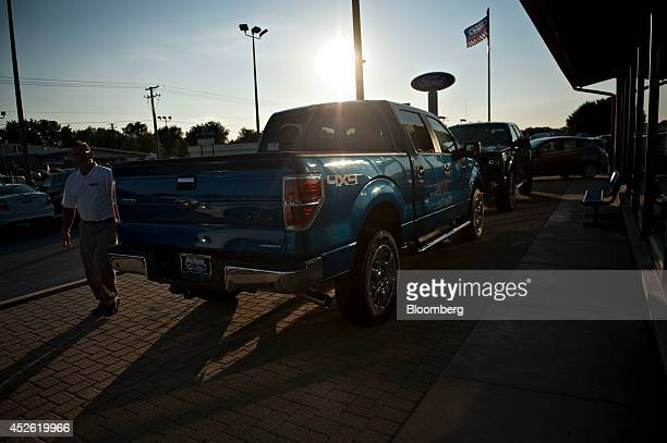 A salesman walks near a Ford Motor Co 2014 F150 pickup truck outside Rod Baker Ford dealership in Plainfield Illinois US on Wednesday July 23 2014...