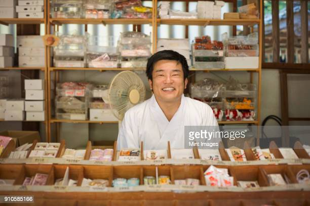 salesman wearing white kimono at shinto sakurai shrine, fukuoka, japan. - shinto shrine stock pictures, royalty-free photos & images