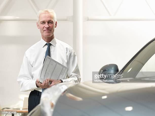 Salesman with car in car dealership
