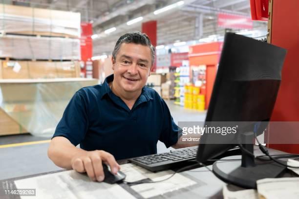vendedor que trabalha em uma loja de ferragem usando um computador e um sorriso - estrutura construída - fotografias e filmes do acervo