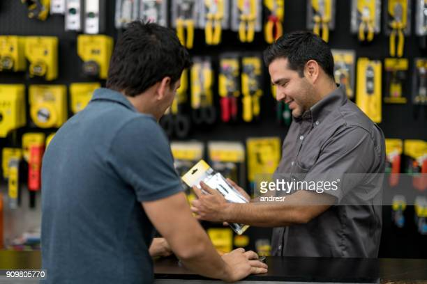 Salesman working at the hardware store and talking to a customer