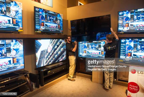Salesmen Eric Freedman and Ryan Porco put a 65'' Samsung on display at Paul's TV and Appliances in Irvine Friday INFO BuyaTV0124kjs Photo by KEVIN...
