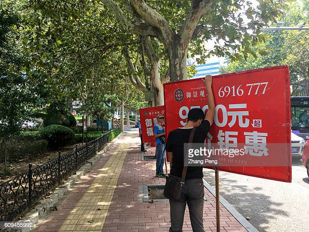 Salesmen holding billboard of new house project to attract pedestrians on the street China's National Bureau of Statistics said that new home sales...