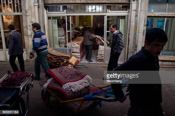Salesmen move trolleys of Persian carpets through the rug bazaar in Tehran Iran on Monday Jan 15 2018 The US presidentplans on stickingwith an...