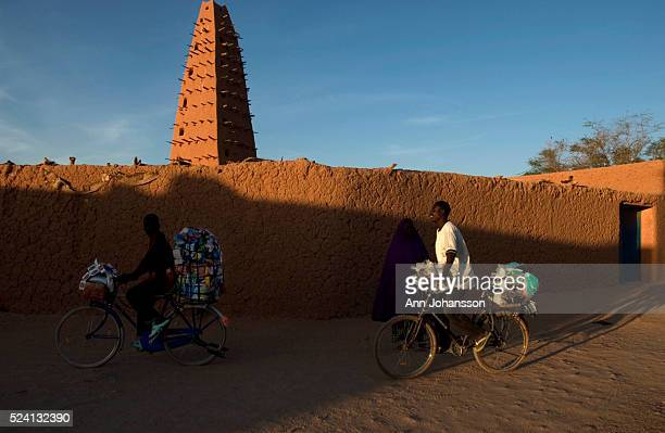 Salesmen ride their bicycles past the Grande Mosquee the Grand Mosque in Agadez Niger The mosque which dates from 1515 but was rebuilt in 1844 is...