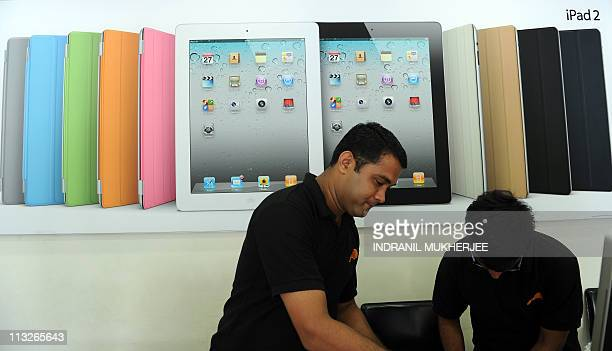 Salesmen standing in front of a poster of the new ipad2 attend to a customer at the counter of an Apple premium reseller outlet in Mumbai on April 29...
