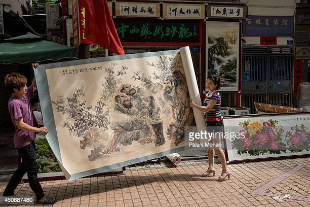 Salespeople at one of the galleries at the artist village in Shenzhen roll out a large Chinese ink drawing to show a customer on June 12 2014 in...