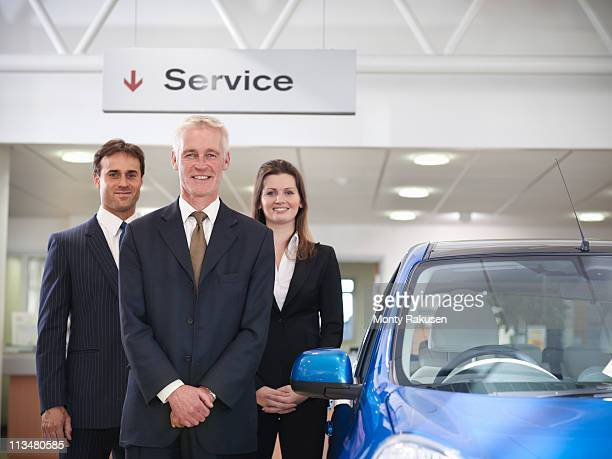 Salespeople under large service sign looking to camera with car in car dealership.