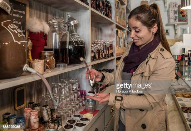 Salesperson Ana Cristina pours Ginja d'Obidos liquor on chocolate cups to participants of Gastronomic FAM Tour on November 27 2017 in Obidos Portugal...