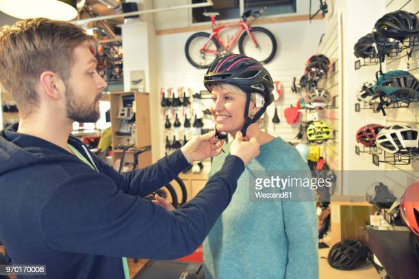 salesperson helping customer with bicycle helmet - cycling helmet stock photos and pictures