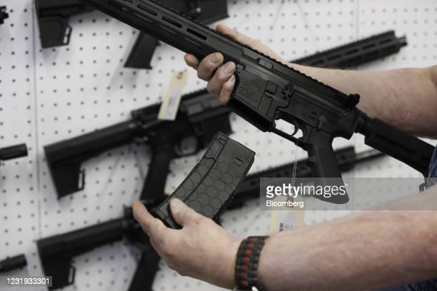 Salesperson holds a high capacity magazine for an AR-15 rifle at a store in Orem, Utah, U.S., on Thursday, March 25, 2021. Two mass shootings in one...