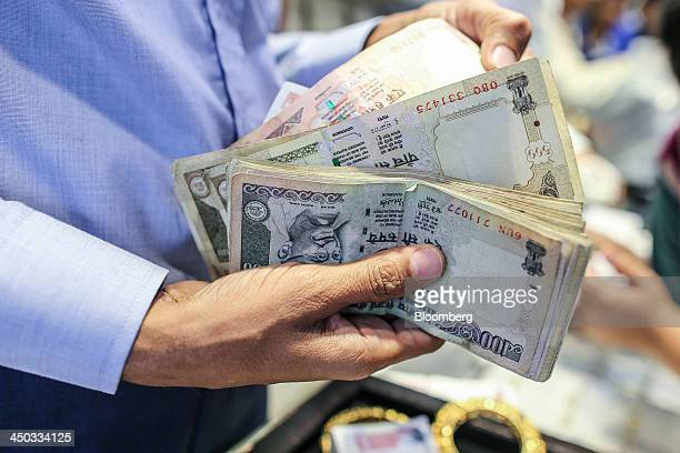 A salesperson holds Indian rupee banknotes of various denominations for a photograph at the Umedmal Tilokchand Zaveri jewelry store during the...
