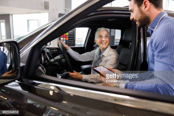 salesperson showing vehicle to potential customer - car dealership stock pictures, royalty-free photos & images