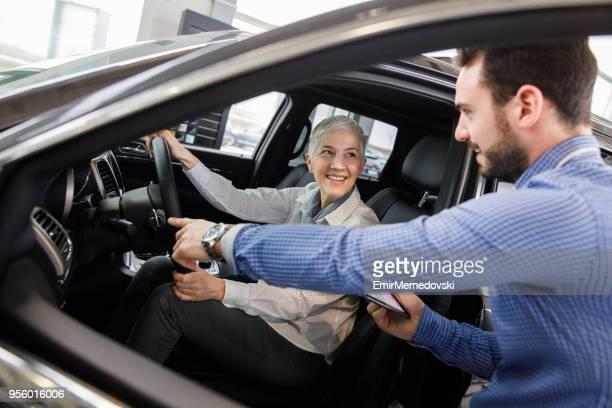 Verkäufer zeigt Fahrzeug mit potenziellen Kunden.