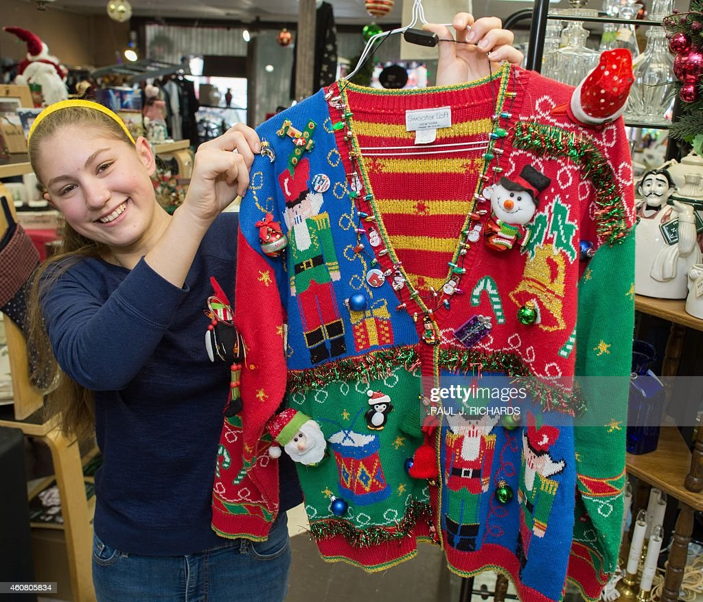 Salesperson Sissi Terryberry holds one of consignment store 'Re-Love It' prized Christmas sweaters December 23, 2014 at their store in Purcellville, Virginia. The growing trend and demand for tacky Christmas sweaters has exploded this year and most stores are completely sold out.