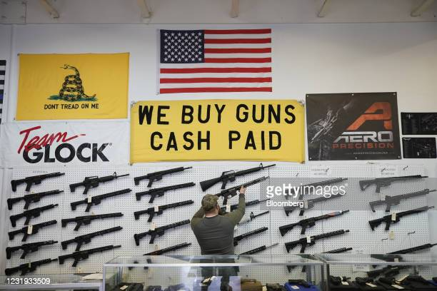 Salesperson takes an AR-15 rifle off the wall at a store in Orem, Utah, U.S., on Thursday, March 25, 2021. Two mass shootings in one week are giving...