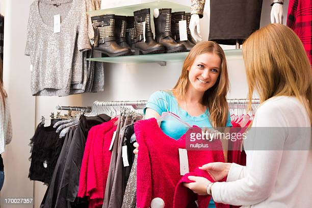 salesperson talking to customers in fashion store