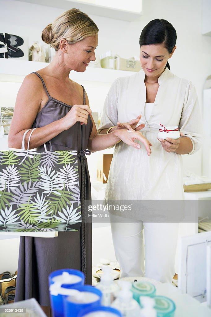 Saleswoman applying lotion to customer's hand : Stock Photo