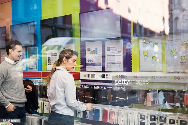 Saleswoman assisting man in buying phone cover seen through glass