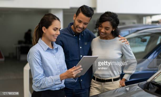 saleswoman at a car dealership talking to a happy couple - car dealership stock pictures, royalty-free photos & images