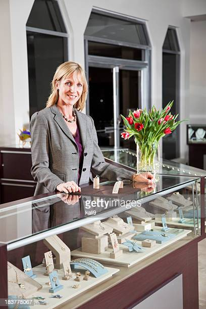 Saleswoman behind counter in jewelry store