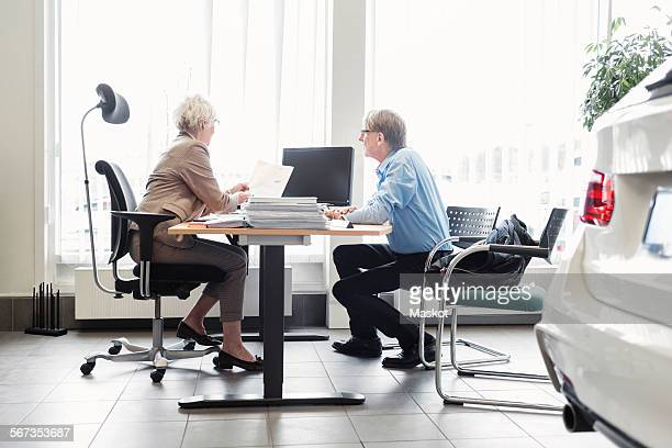 Saleswoman explaining documents at desk to man in car dealership