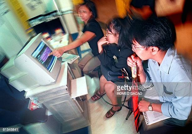 A saleswoman for American computer firm IBM demonstrates a Y2K compliant computer program to several prospective clients in their display booth at...