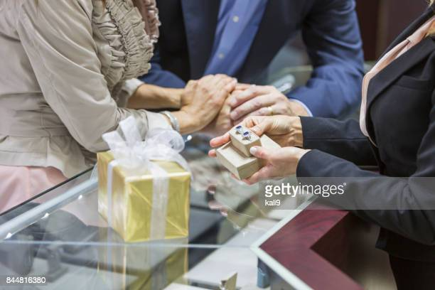 Saleswoman helping couple in jewelry store