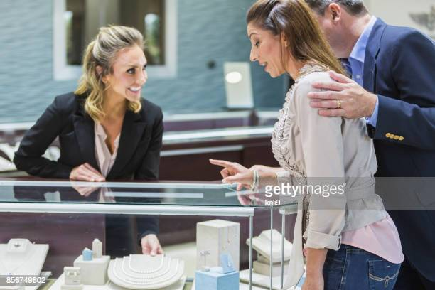 saleswoman helping couple in jewelry store - jewellery products stock photos and pictures