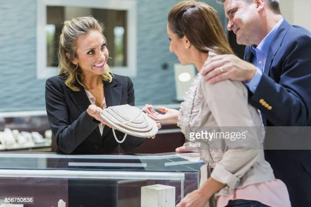 saleswoman helping couple in jewelry store - jewelry store stock pictures, royalty-free photos & images