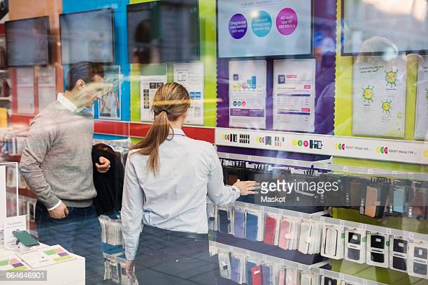 Saleswoman helping customer in buying phone cover seen through glass