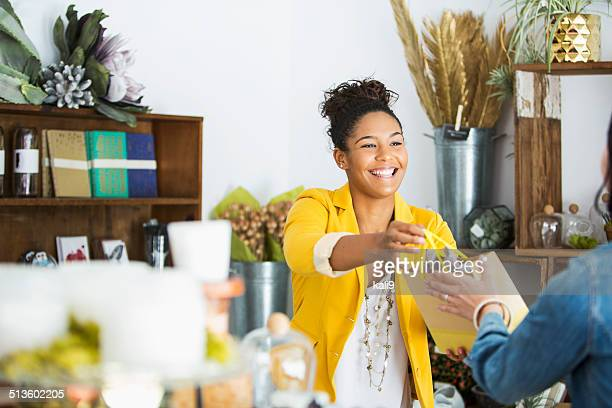 saleswoman helping customer - winkelen stockfoto's en -beelden
