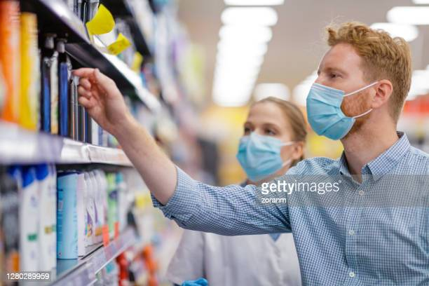 saleswoman helping customer to choose beauty product - face mask beauty product stock pictures, royalty-free photos & images