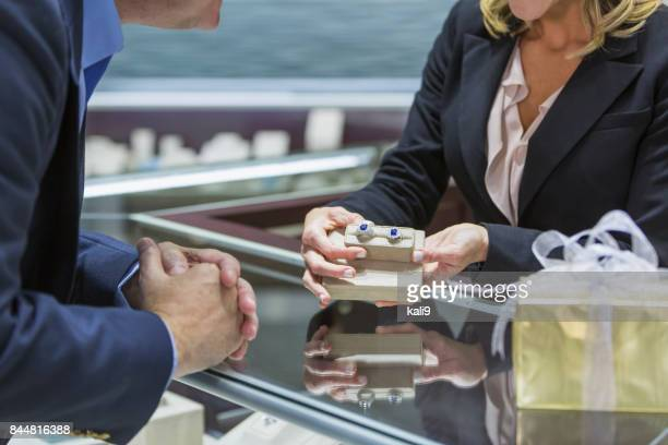 saleswoman helping man shop for jewelry - engagement ring box stock photos and pictures