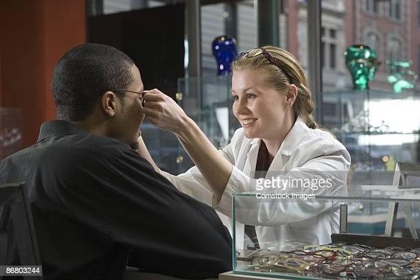 Saleswoman helping man try on eyeglasses