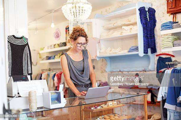 A saleswoman in a boutique working on a laptop