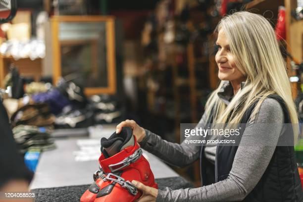 生産シリーズの様々な段階でスキーレンタルと修理工場のセールスウーマン - 賃貸借 ストックフォトと画像