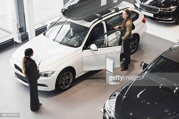 Saleswoman looking at customer examining car in showroom