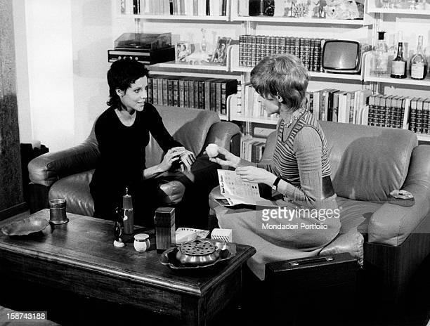 A saleswoman of Avon beauty products showing to a customer how the cosmetics work 1970s