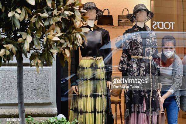 Saleswoman prepares the shop window of Tod's for next opening on May 11, 2020 in Milan, Italy. Italy was the first country to impose a nationwide...