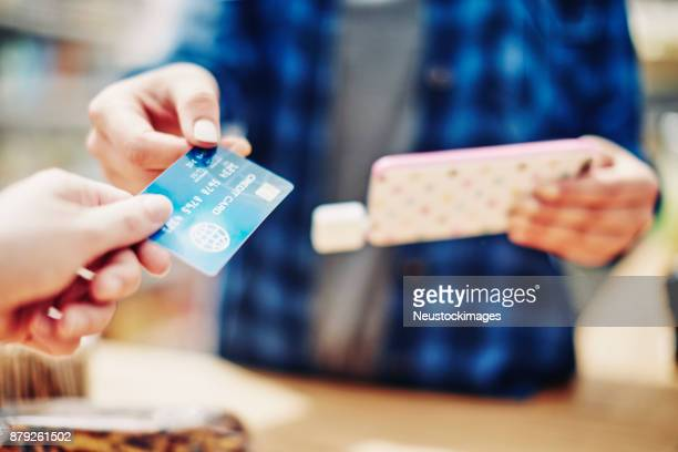 Saleswoman receiving credit card from customer while holding smart phone