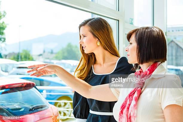 Saleswoman selling car to woman