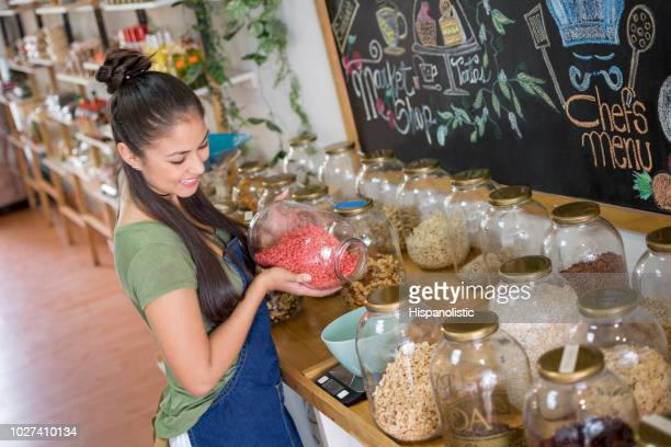 saleswoman selling dried fruits in a healthy food store - hispanolistic stock photos and pictures