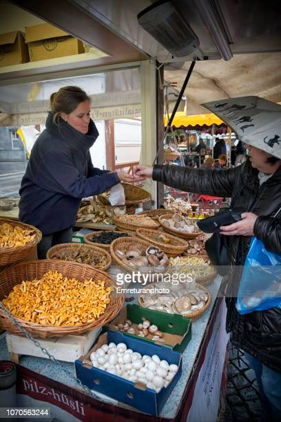 saleswoman selling mushrooms - emreturanphoto stock pictures, royalty-free photos & images