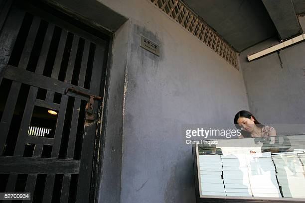 Saleswoman sells introduction books beside a ward at the memorial site of Zhazidong Prison on April 26, 2005 in Chongqing Municipality, China....