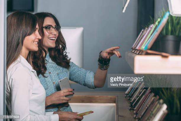 saleswoman standing by female customer looking at phone covers in store - electronics store stock photos and pictures