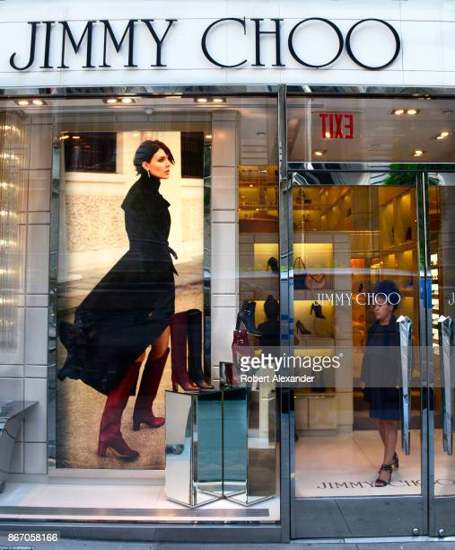 A saleswoman stands at the entrance to the Jimmy Choo shoe store on Fifth Avenue in New York City The designer footwear retailer is know for...