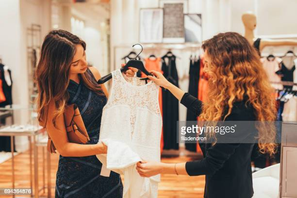 Saleswoman suggesting dress to a customer