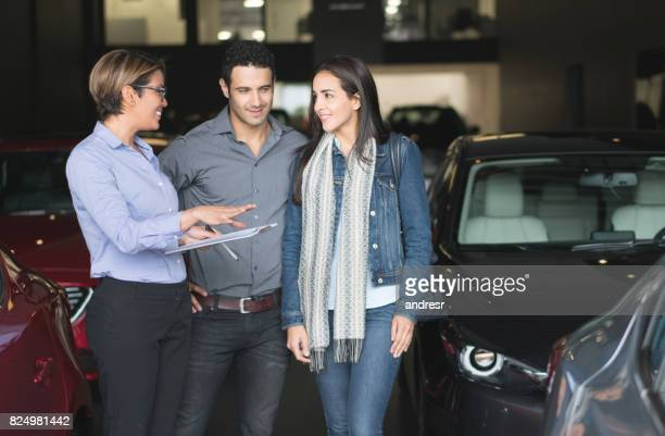 Saleswoman talking to a happy couple and trying to make a sale