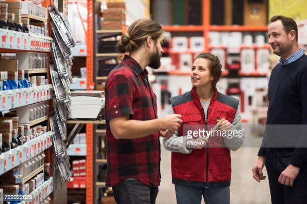 Saleswoman talking to male customers in hardware store